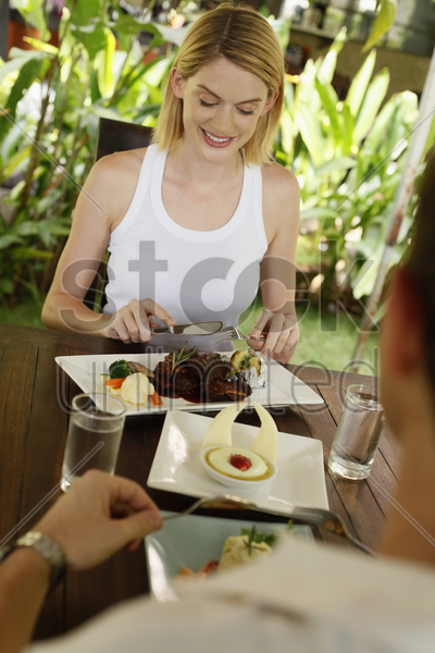 man and woman eating at a cafe stock photo