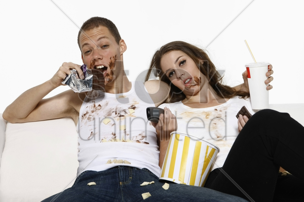 man and woman eating while watching television on couch stock photo