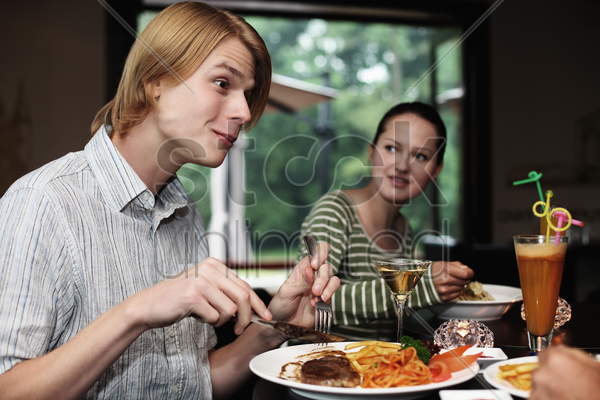 man and woman eating stock photo