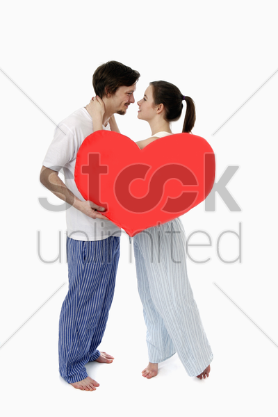 man and woman embracing, man holding a heart shaped cushion stock photo