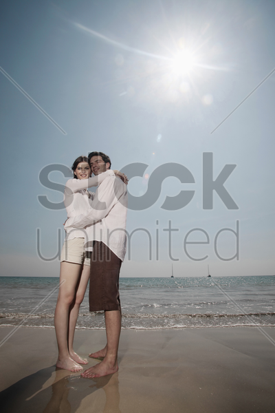 man and woman embracing on the beach stock photo