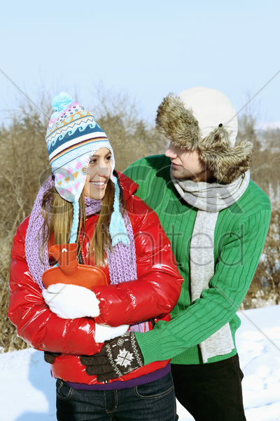 man and woman embracing, woman holding hot water bottle stock photo