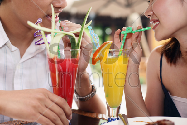 man and woman enjoying their drinks stock photo