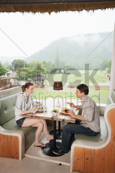 man and woman enjoying their lunch at a restaurant stock photo