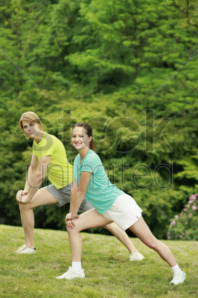man and woman exercising in the park stock photo