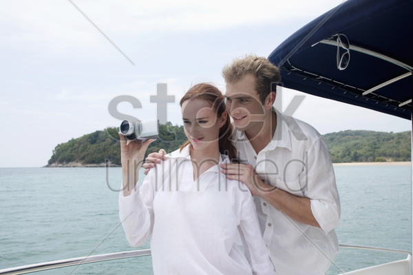 man and woman filming the sea view from speedboat stock photo