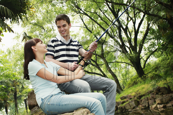 man and woman fishing together stock photo