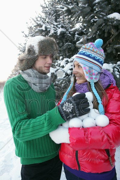 man and woman gathering an armful of snowballs stock photo
