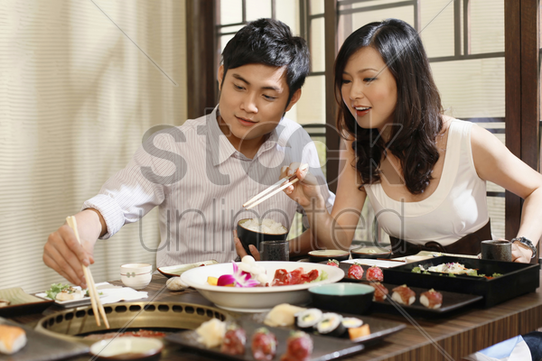 man and woman grilling meat stock photo