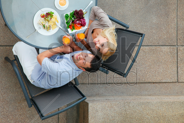 man and woman having a meal at an outdoor restaurant stock photo