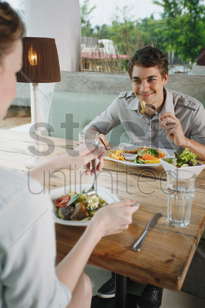 man and woman having lunch together stock photo