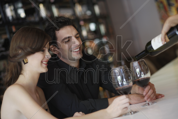 man and woman having their glasses filled up stock photo