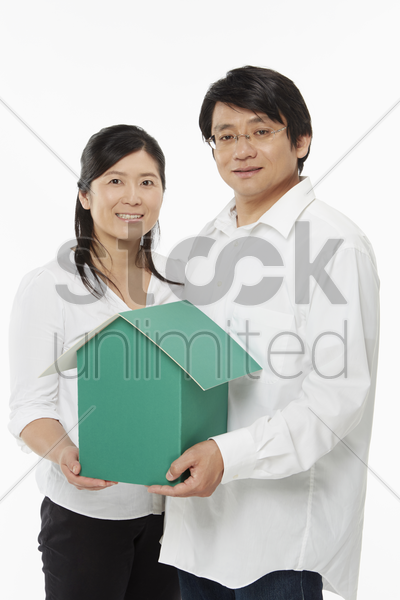 man and woman holding a cardboard house stock photo