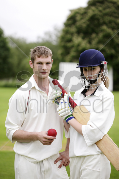 man and woman holding a cricket bat and a cricket ball stock photo