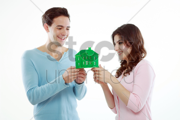 man and woman holding a green house stock photo