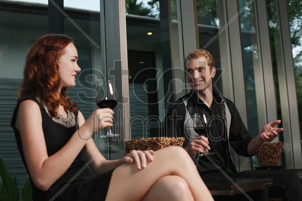 man and woman holding glasses of red wine while chatting stock photo