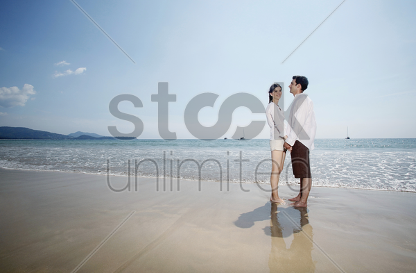 man and woman holding hands and looking at each other stock photo