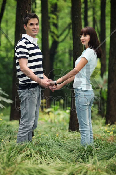 man and woman holding hands in the forest stock photo