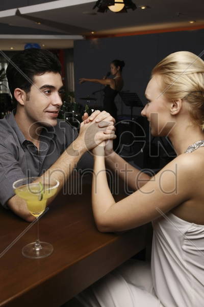 man and woman holding hands while looking at each other stock photo