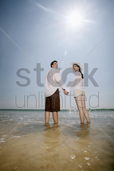 man and woman holding hands while standing at the beach stock photo