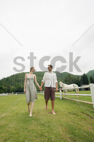 man and woman holding hands while walking stock photo