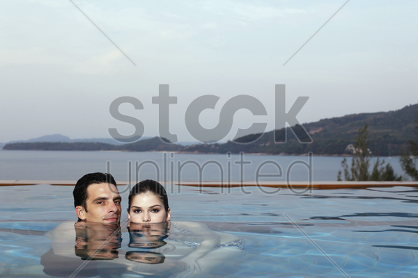 man and woman in pool, heads half submerged in water stock photo