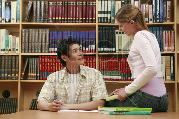 man and woman in the library stock photo