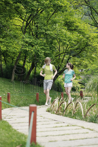 man and woman jogging in the park stock photo