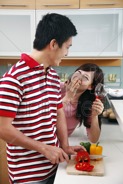 man and woman laughing in kitchen stock photo