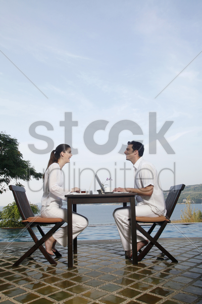 man and woman laughing while using laptop stock photo