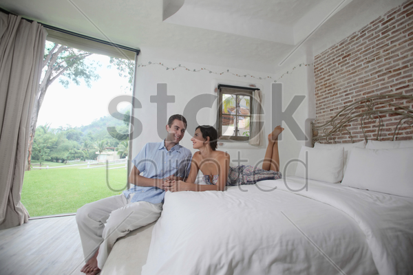 man and woman listening to music on mp3 player stock photo