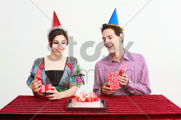 man and woman looking at each other's presents stock photo