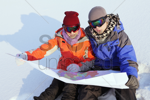 man and woman looking at map stock photo