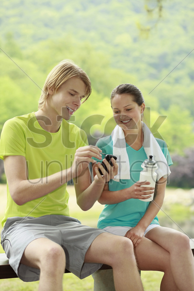 man and woman looking at mobile phone stock photo