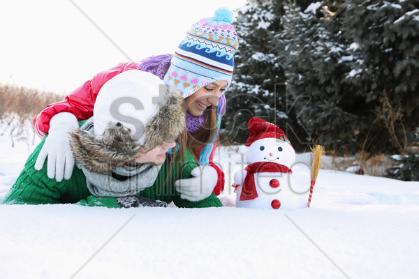 man and woman looking at snowman stock photo