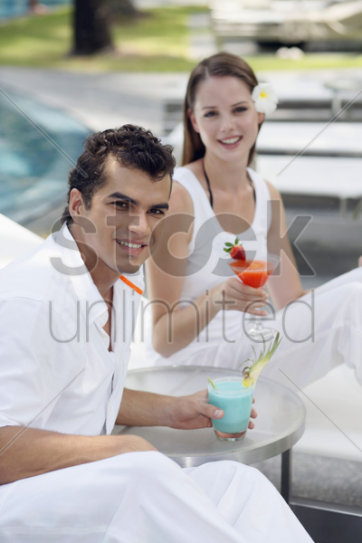 man and woman on lounge chairs with their drinks stock photo
