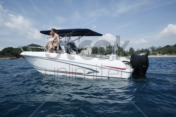 man and woman on speedboat stock photo