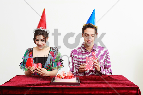man and woman opening their presents stock photo