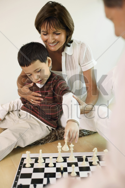man and woman playing chess game with boy stock photo