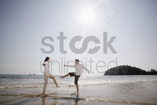 man and woman playing on beach stock photo