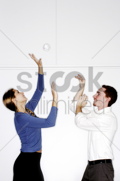 man and woman playing with crumpled paper stock photo