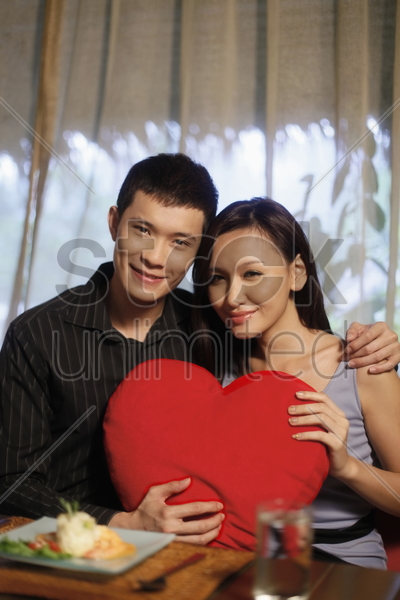 man and woman posing with heart-shaped cushion stock photo