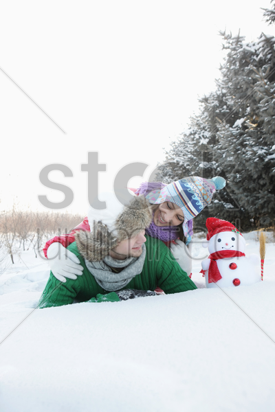 man and woman posing with snowman stock photo