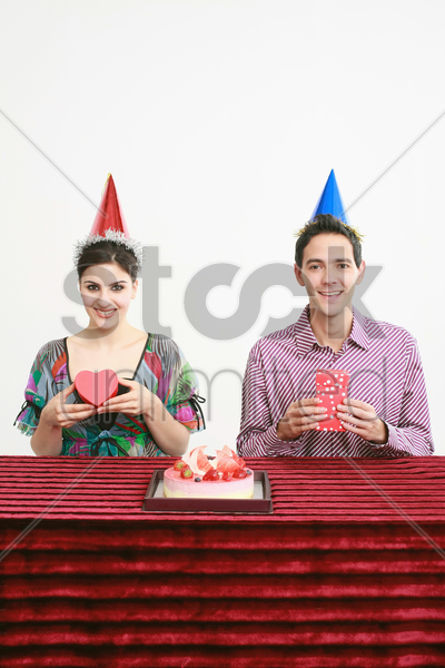man and woman posing with their presents stock photo