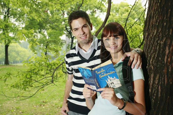 man and woman reading book outdoors stock photo