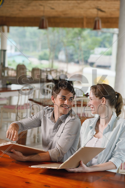 man and woman reading menu in a restaurant stock photo