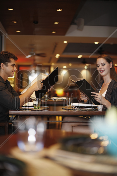 man and woman reading menu in restaurant stock photo