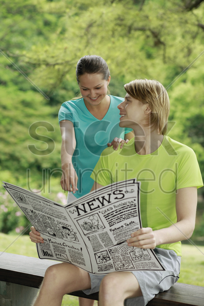 man and woman reading newspaper together stock photo