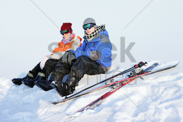 man and woman relaxing after skiing stock photo