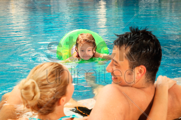 man and woman relaxing at the edge of pool, girl watching them stock photo